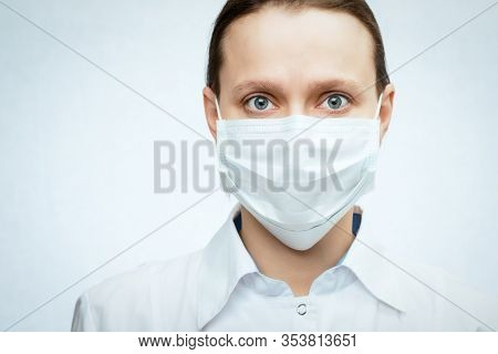 Close-up portrait of scared young female doctor wearing protective surgical mask - epidemic virus outbreak concept