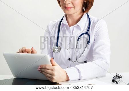 Close Up Female Doctor Hands Using Tablet Computer. Family Physician In White Coat With Stethoscope