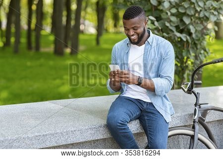 Joyful African American Man Parked Bike Near Bench And Using Smartphone In Park, Texting Or Browsing