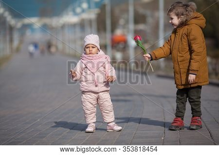 Baby Boy Gives A Tulip Flower To A Little Girl And Smiles. Copy Space. Concept: Spring, Internationa