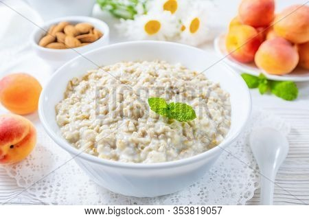 Oatmeal With Apricot And Nuts In Bowl On White Wooden Table.