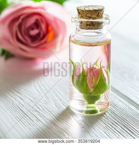 Rose Essential Oil And Rose Flowers On White Wooden Table.