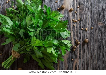 Bunch Of Fresh Parsley And Spices On Dark Wooden Background.