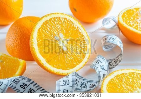 Fresh Sliced And Whole Oranges, And Measuring Tape On White Wooden Table.