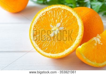 Fresh Oranges And Green Leaves On White Wooden Table.