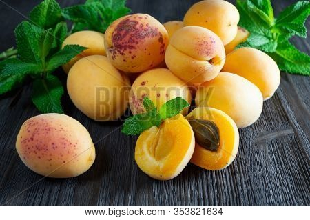 Fresh Apricots And Mint Leaves On Dark Wooden Background.