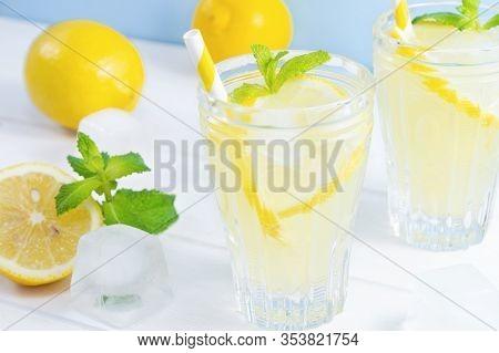 Glasses With Summer Drink Lemonade, Lemon Fruit And Mint Leaves On White Wooden Table.