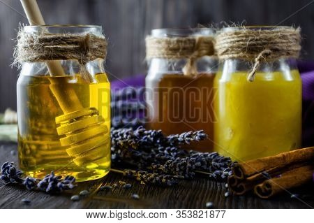 Lavender And Herbal Honey In Glass Jars With Honey Spoon On Dark Wooden Background.