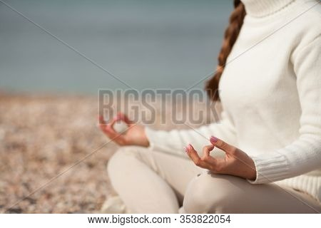 Cute Girl Sitting In The Lotus Position, Meditating, On The Beach. Copy Space. Concept: Yoga, Health