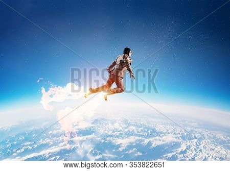 Businessman In Aviator Hat Flying In Cloudy Blue Sky As Superhero. Business Person As Superman With