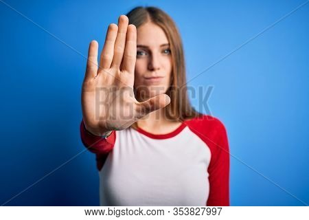 Young beautiful redhead woman wearing casual t-shirt over isolated blue background doing stop sing with palm of the hand. Warning expression with negative and serious gesture on the face.