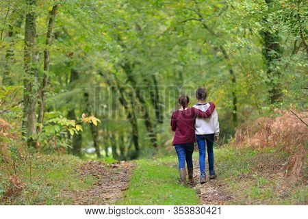 Unidentified two teenagers girls hugging and walking in a temperate forest.