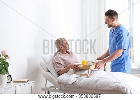 Male Nurse Bringing Food And Medicine For Patient In Hospital Ward. Doctor's Prescription