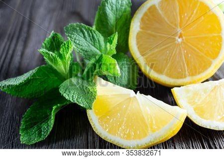 Fresh Lemons And Mint Leaves On Dark Wooden Background.