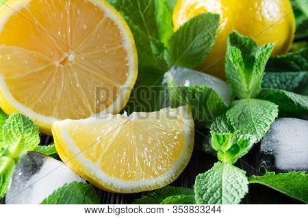 Fresh Lemons, Mint Leaves And Ice Cubes On Wooden Background.