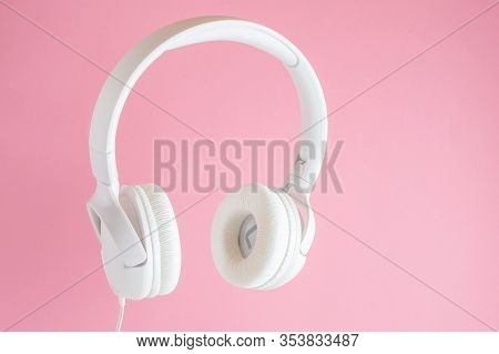 White Headphones On Pink Background. Music Concept.