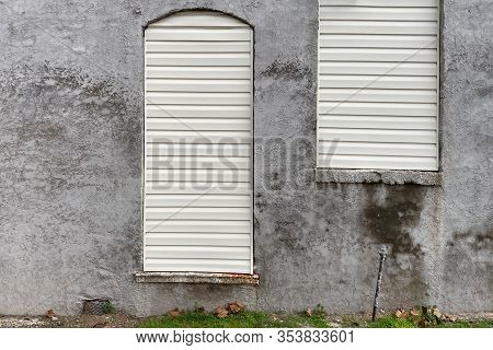 A Pair Of Shut Up Arched Windows On A Gray Cement Warehouse Building Wall With Grass Verge