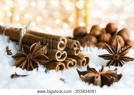 Christmas Spices - Cinnamon Sticks, Star Anise, Cloves And Nuts On The Snow. Christmas Lights In The