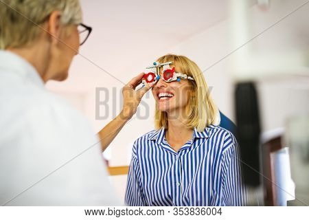 Senior Woman Optometrist Examining Patient In Modern Ophthalmology Clinic