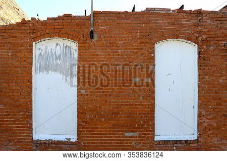 2 Boarded White Windows In An Abandoned Red Brick Wall