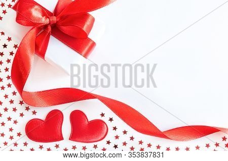 Gift Or Present Box With Red Ribbon, Decorative Hearts And Stars Confetti On White Background. Holid