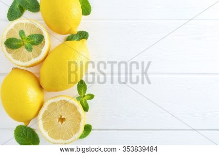 Fresh Sliced And Whole Lemons And Mint Leaves On White Wooden Background. Flat Lay, Top View, Copy S