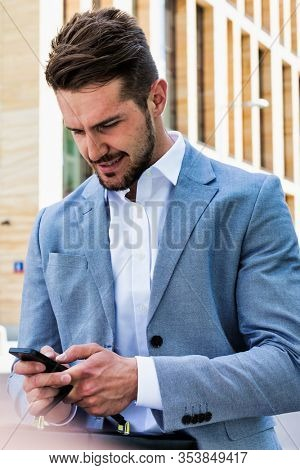 Young handsome businessman using smartphone against office building