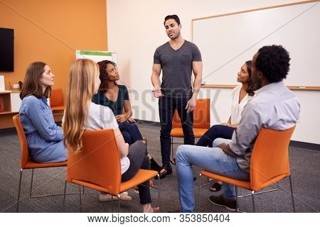 Man Standing To Address Group Of Men And Women At Mental Health Group Therapy Meeting