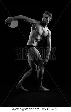 Side View Of Young Athletic Man With Perfect Body And Tensed Muscles Throwing Discus. Monochrome Por