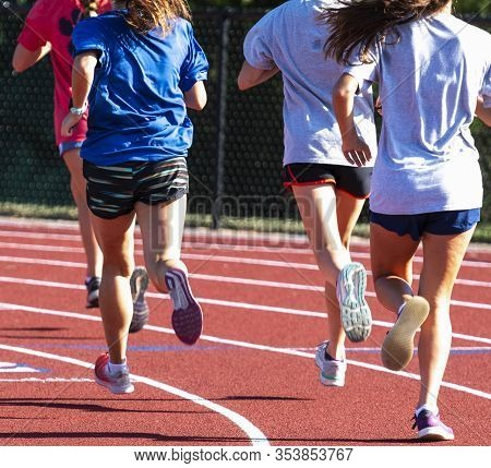 Rear View Of A Group Of High School Track Girls Running Together On A Red Track While Running Interv