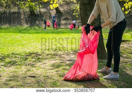Man And Woman Volunteer Wearing Picking Up Trash And Plastic Waste In Public Park. Young People Wear