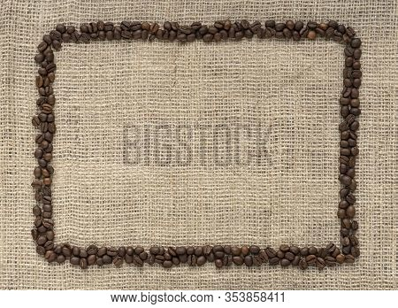 Fresh Coffee Bean Is On The Burlap Sack Background, Top View. Coffee Beans Boarder. Coffee Frame.