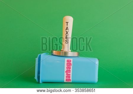 A Mallet With The Word Taxes Compresses Crushes A Garbage Can /a Mallet With The Word Taxes Compress