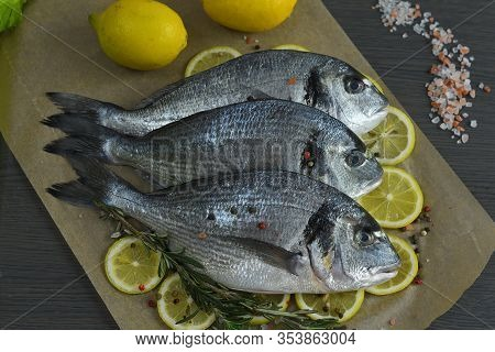 Raw Fish With Aromatic Herbs, Spices, Salt And Lime Slices.raw Dorado On Dark Background, Healthy Fo