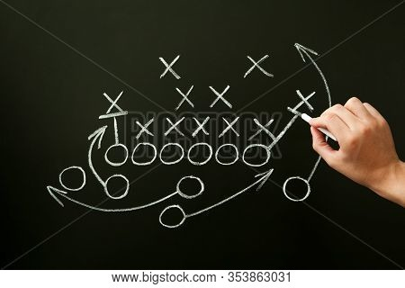 Coach Drawing American Football Or Rugby Game Playbook, Strategy And Tactics With Chalk On Blackboar