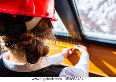 Close Up On Female Construction Inspector Wearing Red Hard Hat As She Checking The Window Using A Ta