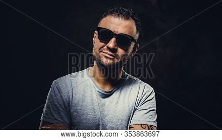 Close Up Portrait Of A Smirking Adult Man Wearing Grey T-shirt And Sunglasses, Looking Straight Into