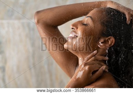Young woman taking shower relaxing under warm running water. Smiling beautiful black woman enjoy during hot water bath. Happy girl with closed eyes in shower rinse shampoo with water dripping on face.