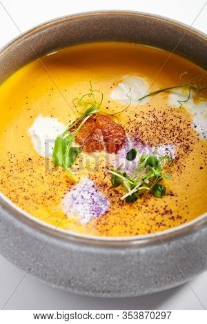 Pumpkin soup in bowl. Served main course. Vegetable cream soup with Italian stracciatella cheese. Restaurant food decorated with herbs composition. Dinner, gourmet meal in plate