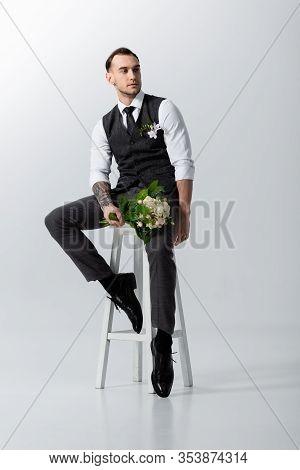 Handsome Tattooed Elegant Bridegroom With Bouquet Sitting On Highchair On Grey