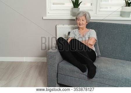 Grandmother With Gray Hair Is Sitting On A Gray Sofa. Sad Korean Grandmother Looks Into The Distance