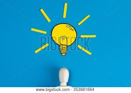 Wooden Figurine Of A Man With A Light Bulb With Yellow Craft Paper Over His Head On A Blue Backgroun