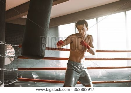 Male Boxer Training With Punching Bag In Dark Sports Hall. Young Boxer Training On Punching Bag. Mal