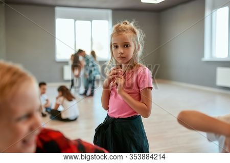 Portrait Of A Little Cute Girl Looking At Camera While Standing In The Dance Studio. Group Of Childr