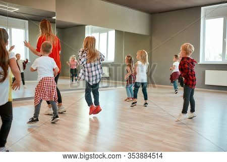 Group Of Active Children Dancing In Front Of The Large Mirror While Having Choreography Class In The