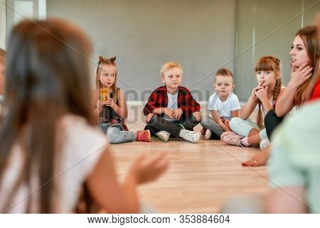 Full Length Portrait Of Cute Little Boys And Girls Sitting On The Floor Gathered Around Their Female