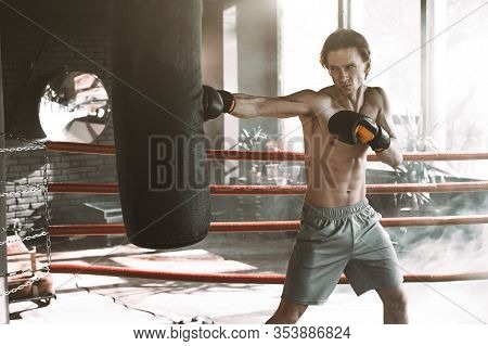Male Caucasian Boxer Punching A Boxing Bag In Boxing Studio With Bright Light. Sport, Fitness, Healt