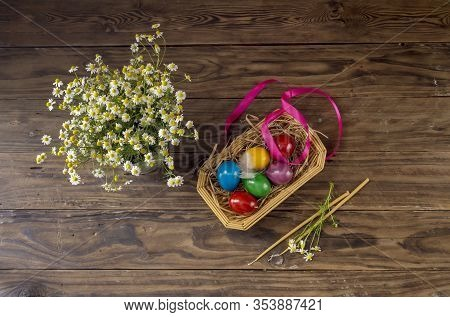 The Easter Composition. Eggs, A Flowering Daisies And Church Candles On Wooden Table Close-up.