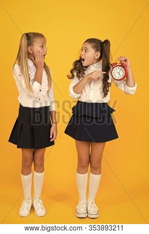 We Are Late For Class. Stressed Small Children Pointing At Clock That Running Late On Yellow Backgro
