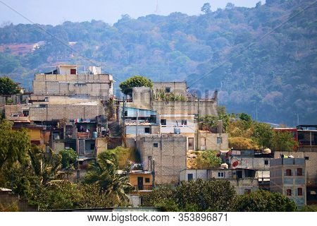February 25, 2020 In Amititlan, Guatemala:  Shacks And Homes On A Hillside Overlooking Forested Hill